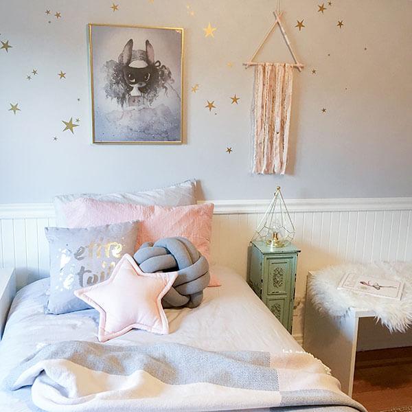 Sur un lit de chambre de fille des coussins et étoiles sur les murs