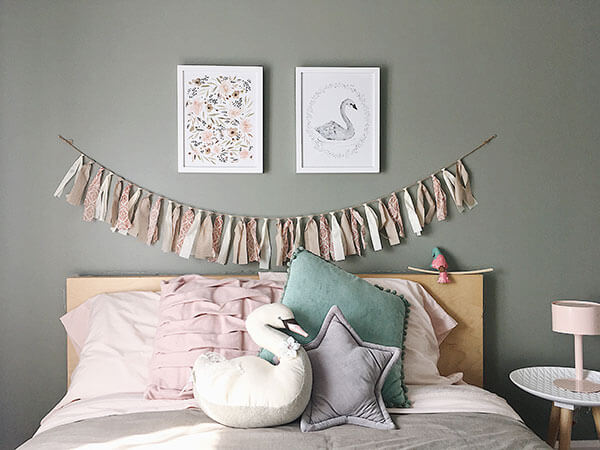 Guirlande de retailles de tissus tons de rose et coussins cygne sur le lit chambre fillette