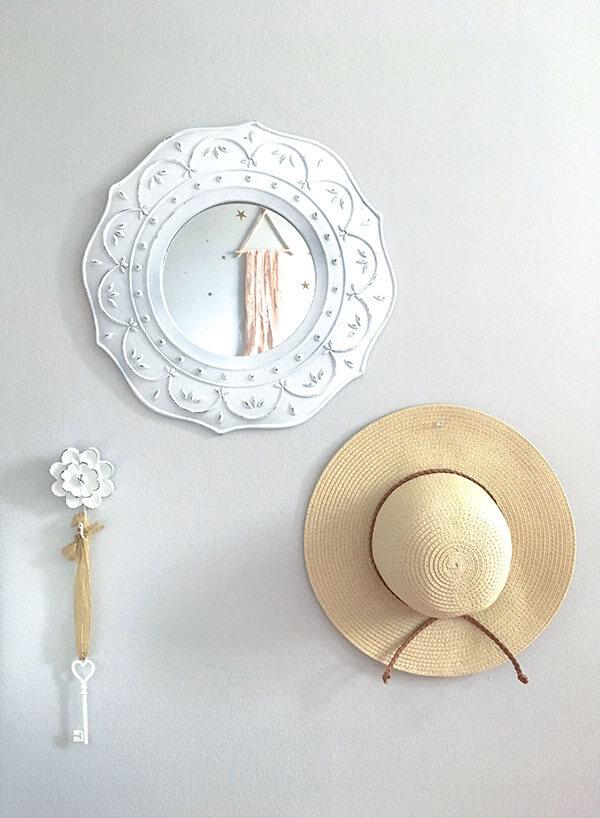 Un miroir blanc et un chapeau de paille sur le mur d'une chambre de fille