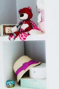 Sur une tablette des objets qui décorent la chambre d'une fillette ourson et chapeau rose