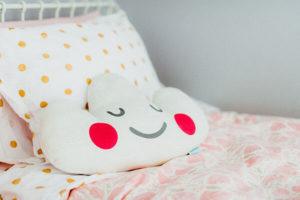 Coussin sourire sur lit de déco de chambre de fille