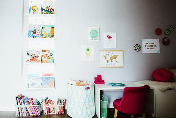 Décor chambre fille fauteuil rose coin bureau livres enfants