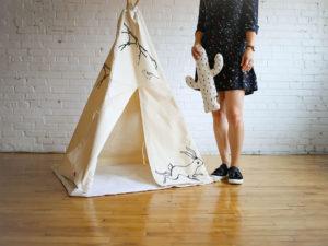 Femme debout près d'un tipi sur fond blanc et bois