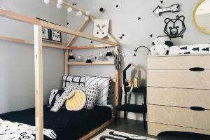 Coin de la chambre de garçon avec un lit en bois et déco d'artisans québécois