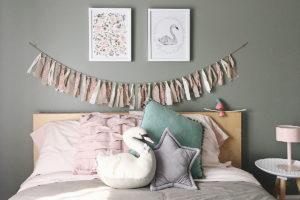 Plan de face d'un lit de fillette décoré avec des tons doux et pastel